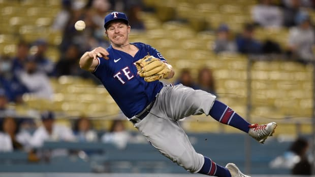 Jun 11, 2021; Los Angeles, California, USA; Texas Rangers second baseman Brock Holt (16) dives while attempting to throw out Los Angeles Dodgers left fielder AJ Pollock (11) at first base during the eighth inning at Dodger Stadium.