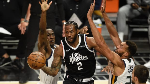 Jun 12, 2021; Los Angeles, California, USA; LA Clippers forward Kawhi Leonard (2) passes the ball while defended by Utah Jazz guard Miye Oni (81) and center Rudy Gobert (27) in the first quarter during game three in the second round of the 2021 NBA Playoffs. at Staples Center. Mandatory Credit: Kelvin Kuo-USA TODAY Sports
