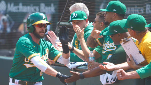Oakland Athletics second baseman Jed Lowrie (8) high-fives teammates after scoring a run against the Los Angeles Angels during the sixth inning at RingCentral Coliseum.