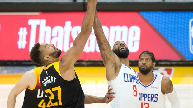 Jun 16, 2021; Salt Lake City, Utah, USA; Utah Jazz center Rudy Gobert (27) and LA Clippers forward Marcus Morris Sr. (8) compete for a jump ball to start game five in the second round of the 2021 NBA Playoffs at Vivint Arena. Mandatory Credit: Russell Isabella-USA TODAY Sports