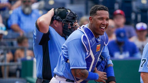 Jun 20, 2021; Kansas City, Missouri, USA; Kansas City Royals catcher Salvador Perez (13) laughs as he assures the umpires he s not hurt after getting hit with a foul tip in the seventh inning against the Boston Red Sox at Kauffman Stadium. Mandatory Credit: Denny Medley-USA TODAY Sports