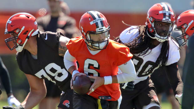 Cleveland Browns quarterback Baker Mayfield (6) looks to make a hand off to a running back under pressure from defensive end Jadeveon Clowney during an NFL football practice at the team's training facility, Wednesday, June 16, 2021, in Berea, Ohio. Browns 1
