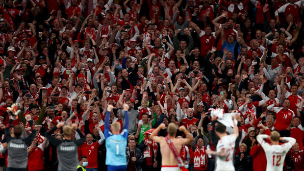 Denmark fans celebrate with players at Parken Stadium