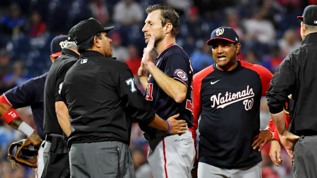 Jun 22, 2021; Philadelphia, Pennsylvania, USA; Washington Nationals  pitcher Max Scherzer (31) and manager Dave Martinez (4) talk with umpire Alfonso Marquez (72) as they check for a foreign substance on Scherzer during the middle of the fourth inning against the Philadelphia Phillies at Citizens Bank Park.