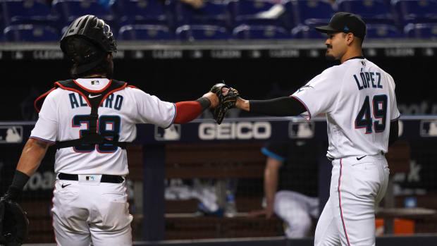 Miami Marlins catcher Jorge Alfaro (38) and Miami Marlins starting pitcher Pablo Lopez (49) fist bump while leaving the field after the 8th inning at loanDepot park against the Colorado Rockies.