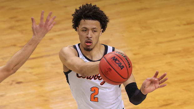 Oklahoma State Cowboys guard Cade Cunningham (2) passes the ball past Liberty Flames forward Kyle Rode (22) during the first round of the 2021 NCAA Tournament at Indiana Farmers Coliseum.