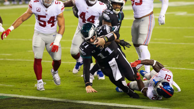 Oct 22, 2020; Philadelphia, Pennsylvania, USA; Philadelphia Eagles quarterback Carson Wentz (11) runs for a touchdown past New York Giants strong safety Jabrill Peppers (21) during the first quarter at Lincoln Financial Field.