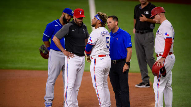 Jun 26, 2021; Arlington, Texas, USA; Texas Rangers manager Chris Woodward (8) checks on Rangers designated hitter Willie Calhoun (5) after Calhoun is hit by a pitch during the second inning against the Kansas City Royals at Globe Life Field.