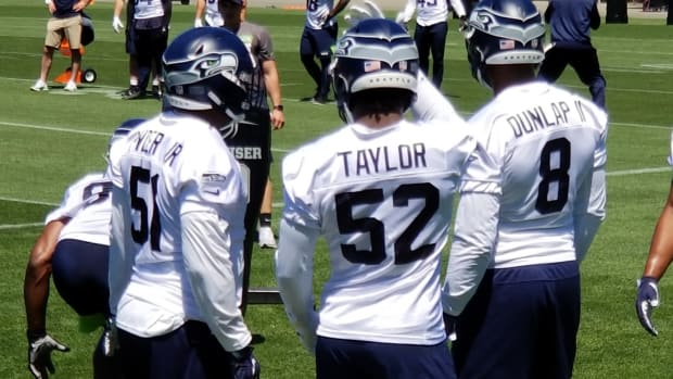 Kerry Hyder chats with Darrell Taylor and Carlos Dunlap during Seahawks' minicamp practice.