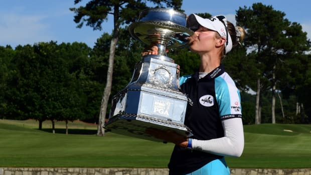 Nelly Korda poses with the championship trophy as she celebrates winning the KPMG Women's PGA Championship golf tournament at the Atlanta Athletic Club.