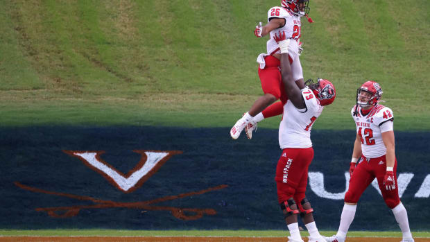 Oct 10, 2020; Charlottesville, Virginia, USA; North Carolina State Wolfpack running back Trent Pennix (26) celebrates with Wolfpack offensive lineman Ikem Ekwonu (79) after scoring a touchdown against the Virginia Cavaliers in the first quarter at Scott Stadium.
