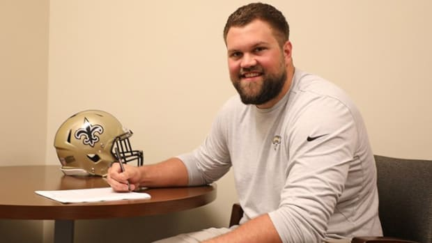 Ryan Ramczyk signing his contract extension with Saints