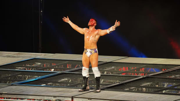 A bloodied MJF stands on top of a steel cage after throwing Chris Jericho from the top