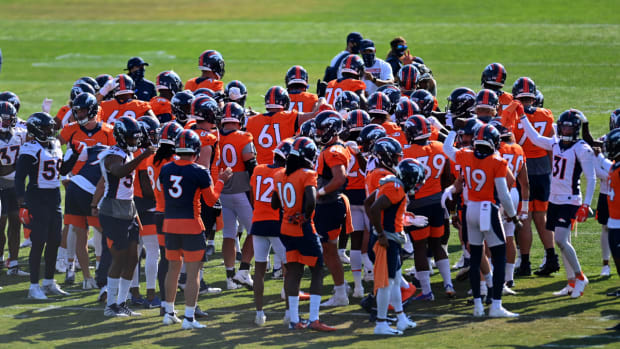 Members of the Denver Broncos huddle during training camp at the UCHealth Training Center