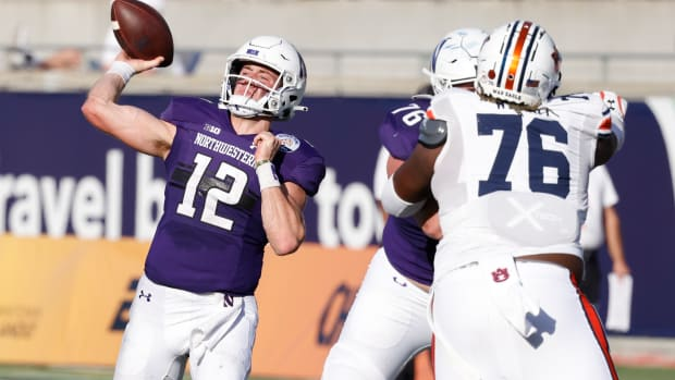 Northwestern Wildcats quarterback Peyton Ramsey (12) throws a pass as Northwestern Wildcats offensive lineman Ethan Wiederkehr (76) blocks Auburn Tigers defensive tackle Jeremiah Wright (76) during the second half at Camping World Stadium.