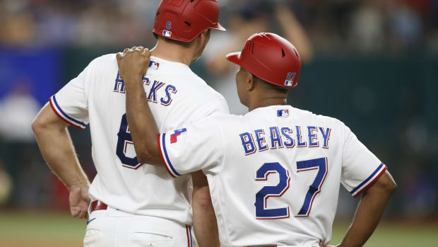 Jul 6, 2021; Arlington, Texas, USA; Texas Rangers third base coach Tony Beasley (27) talks with catcher John Hicks (6) after he reached third base in the seventh inning against the Detroit Tigers at Globe Life Field.