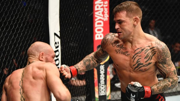 Dustin Poirier punches Conor McGregor of Ireland in a lightweight fight during the UFC 257 event inside Etihad Arena on UFC Fight Island.