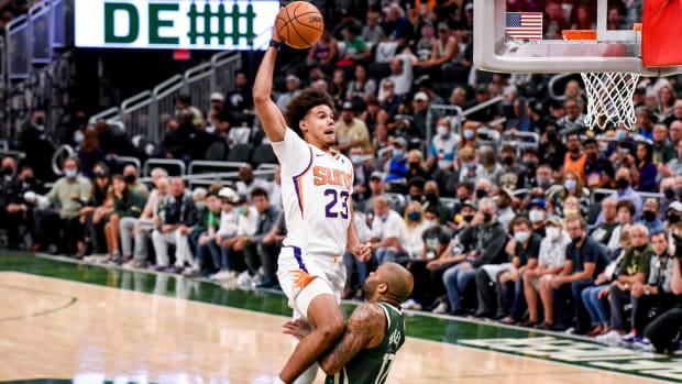 Suns' Cam Johnson dunks on Bucks' forward PJ Tucker