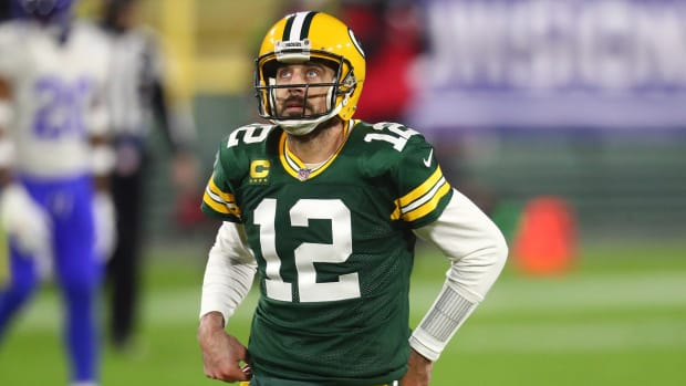 Aaron Rodgers looks up at the scoreboard during a 2020 playoff game against the Rams