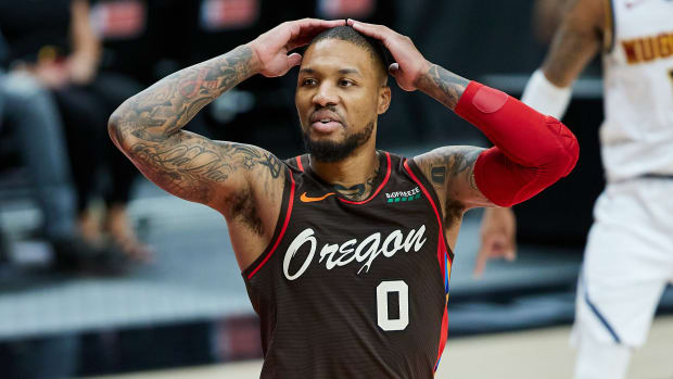 Portland Trail Blazers guard Damian Lillard (0) reacts after being called for a foul against the Denver Nuggets during the third quarter at the Moda Center.