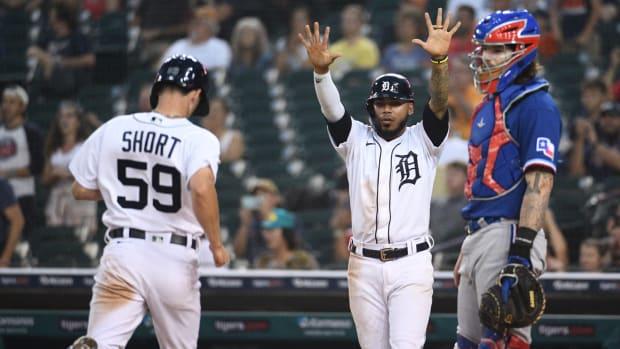 Jul 19, 2021; Detroit, Michigan, USA; Detroit Tigers pitch runner Zack Short (59) scores a run as shortstop Harold Castro (30) and Texas Rangers catcher Jonah Heim (28) watch during the sixth inning at Comerica Park.