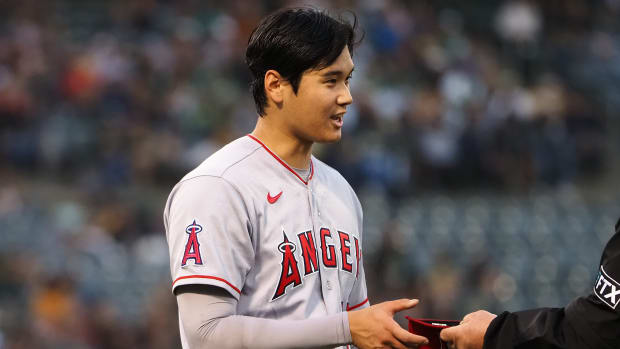 Shohei Ohtani's hat is inspected by an umpire