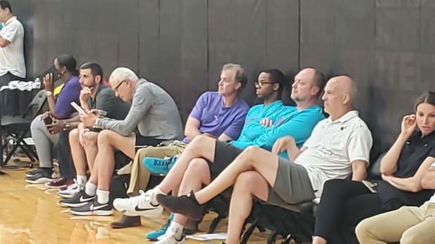 FILE— Charlotte Hornets assistant GM Buzz Peterson, dressed in a purple shirt and leaning back in his chair, watches prospects during a workout in this June 5, 2019 file photo. (Roderick Boone/File)