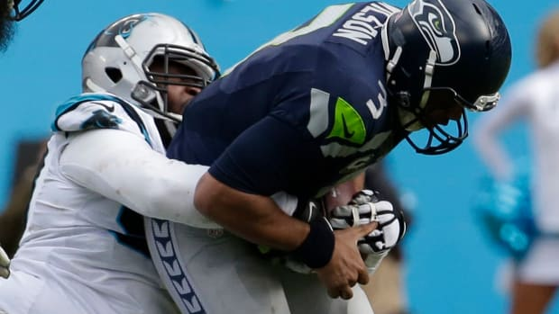 Seattle Seahawks quarterback Russell Wilson (3) is brought down by Carolina Panthers defensive tackle Kawann Short (99) during the second quarter in a NFC Divisional round playoff game at Bank of America Stadium.
