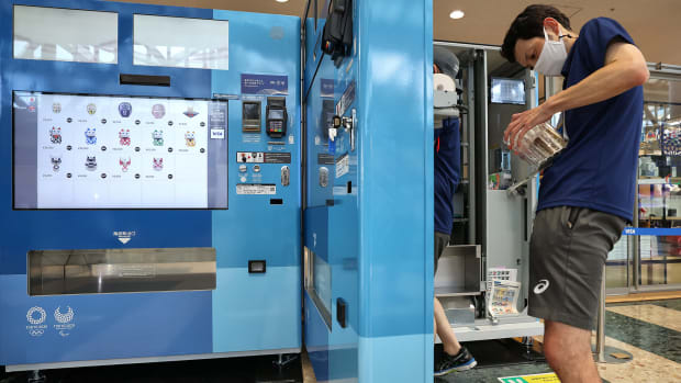 A worker restocks a vending machine at the Tokyo Olympics.