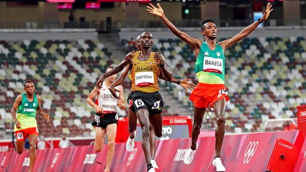 Selemon Barega crosses the finish line ahead of Joshua Cheptegei to win gold in the 10,000 meters at the Tokyo Olympics