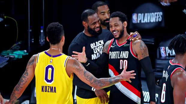 Carmelo Anthony (00) greeting Kyle Kuzma and LeBron James.