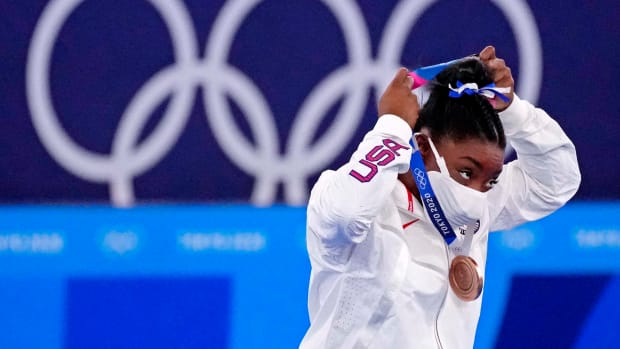 Simone Biles putting on her bronze medal.