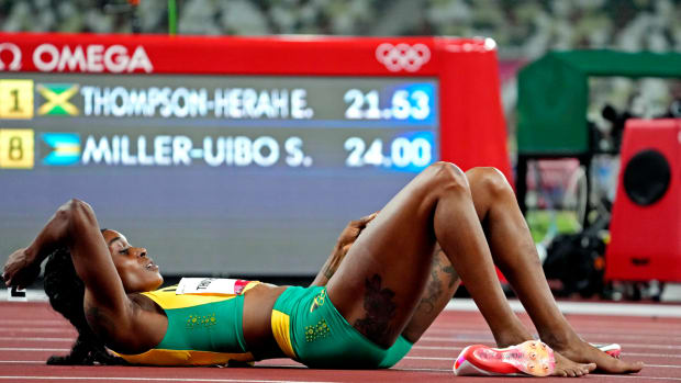 Elaine Thompson on the ground after defending her Olympic gold medal in the women's 200 meters.