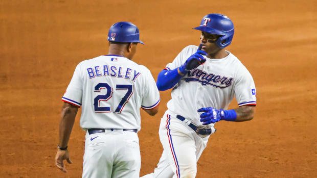 Aug 3, 2021; Arlington, Texas, USA; Texas Rangers second baseman Andy Ibanez (77) celebrates with third base coach Tony Beasley (27) after hitting a home run during the sixth inning against the Los Angeles Angels at Globe Life Field.