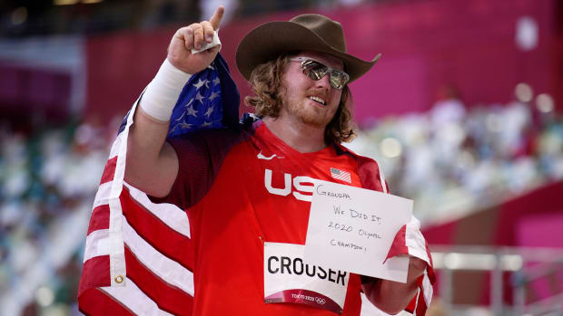 Shot putter Ryan Crouser holds a sign for his grandfather after winning the gold medal