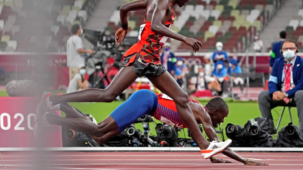 Paul Chelimo leans at the finish line to win bronze in the men's 5,000 meters at the Tokyo Olympics.