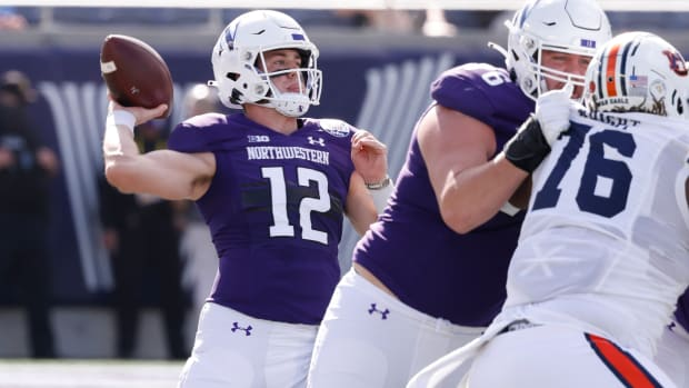 Northwestern Wildcats offensive lineman Ethan Wiederkehr (middle) blocks Auburn Tigers defensive tackle Jeremiah Wright (76) as Wildcats quarterback Peyton Ramsey (12) throws a pass during the first quarter at Camping World Stadium. Reinhold Matay-USA TODAY Sports