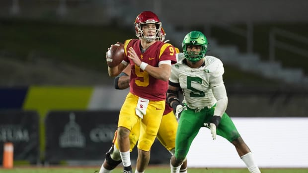 Dec 18, 2020; Los Angeles, California, USA; Southern California Trojans quarterback Kedon Slovis (9) is pressured by Oregon Ducks defensive end Kayvon Thibodeaux (5) in the second half during the Pac-12 Championship at United Airlines Field at Los Angeles Memorial Coliseum. Oregon defeated USC 31-24.
