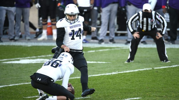 Northwestern Wildcats kicker Charlie Kuhbander (14) kicks a field goal as punter Derek Adams (36) holds the football during the second quarter against the Michigan State Spartans at Spartan Stadium. Tim Fuller-USA TODAY Sports