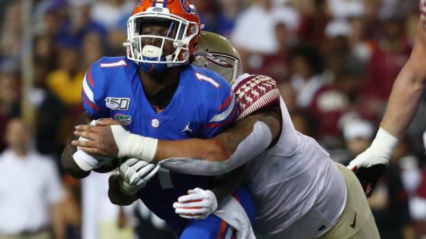 Nov 30, 2019; Gainesville, FL, USA; Florida State Seminoles defensive tackle Cory Durden (16) tackles Florida Gators wide receiver Kadarius Toney (1) during the first quarter at Ben Hill Griffin Stadium.