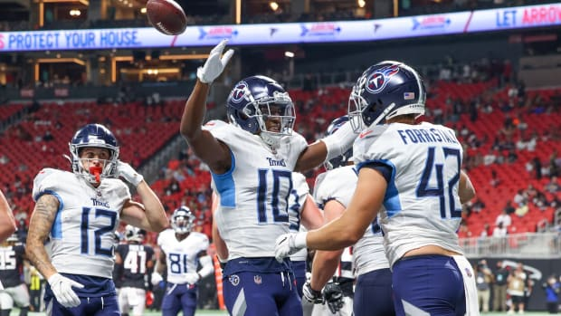 Tennessee Titans tight end Miller Forristall (42) celebrates his touchdown with wide receiver Dez Fitzpatrick (10) during their game against the Atlanta Falcons at Mercedes-Benz Stadium. Also shown on the play is Tennessee Titans wide receiver Mason Kinsey (12).