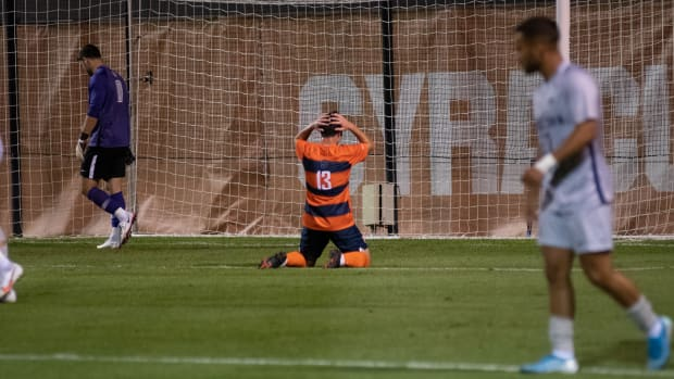 Syracuse's Colin Biros sits on his knees in front of the goal