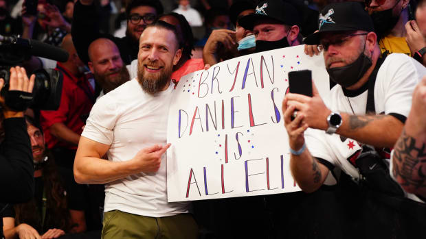 """Bryan Danielson poses with a fan's sign after his AEW debut at """"All Out"""""""