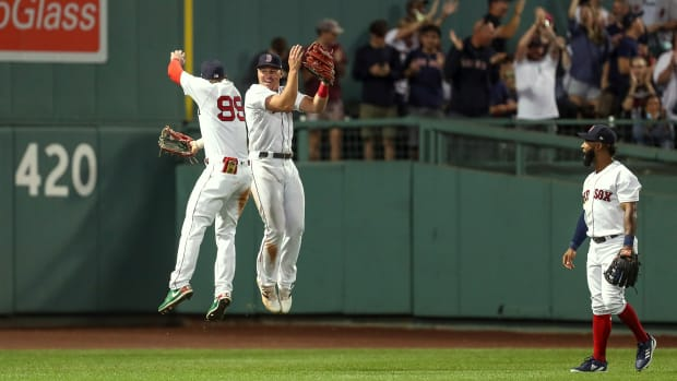 Hunter Renfroe celebrates by jumping in the air with a teammate