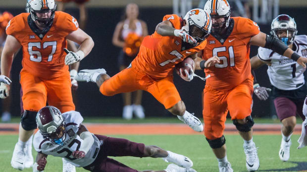 Sep 4, 2021; Stillwater, Oklahoma, USA; Oklahoma State Cowboys running back Jaylen Warren (7) is tripped up by Missouri State Bears cornerback Lemondre Joe (22) as Oklahoma State Cowboys offensive lineman Cole Birmingham (67) and offensive lineman Danny Godlevske (51) look on during the fourth quarter at Boone Pickens Stadium. Oklahoma State Cowboys beat Missouri State Bears 23-16. Mandatory Credit: Brett Rojo-USA TODAY Sports