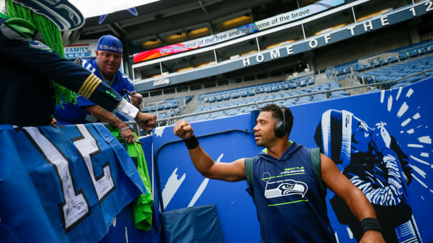 Aug 21, 2021; Seattle, Washington, USA; Seattle Seahawks quarterback Russell Wilson (3) bumps fists with fans after signing autographs during pregame warmups against the Denver Broncos at Lumen Field.