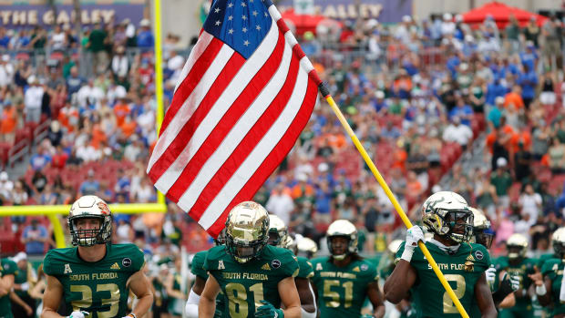 Sep 11, 2021; Tampa, Florida, USA; South Florida Bulls defensive back TJ Robinson (2) carries an American flag in remembrance of 9/11 during the first half against the Florida Gators at Raymond James Stadium.