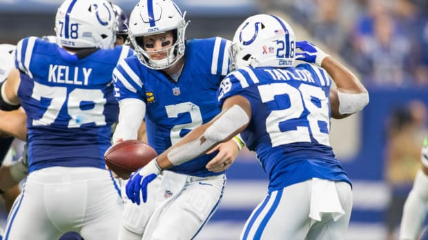 Sep 12, 2021; Indianapolis, Indiana, USA; Indianapolis Colts quarterback Carson Wentz (2) hands the ball off to running back Jonathan Taylor (28) in the second half against the Seattle Seahawks at Lucas Oil Stadium.