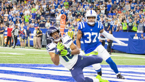 Sep 12, 2021; Indianapolis, Indiana, USA; Seattle Seahawks wide receiver Tyler Lockett (16) catches a touchdown pass while Indianapolis Colts safety Khari Willis (37) defends in the first quarter at Lucas Oil Stadium. Mandatory Credit: Trevor Ruszkowski-USA TODAY Sports