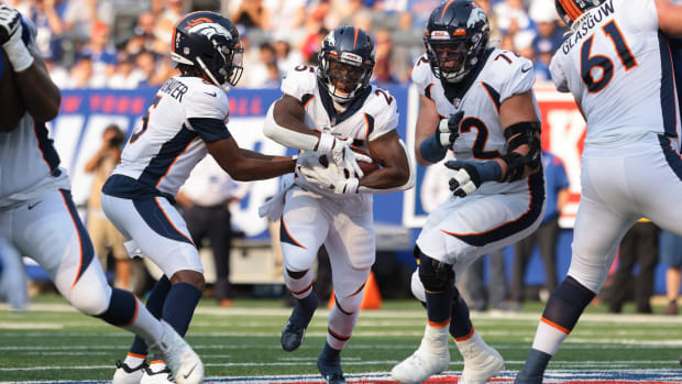 Denver Broncos quarterback Teddy Bridgewater (5) hands off to running back Melvin Gordon (25) during the first quarter against the New York Giants at MetLife Stadium.